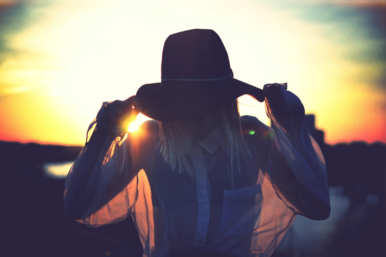 日没の前に彼女の顔を覆っている帽子の女