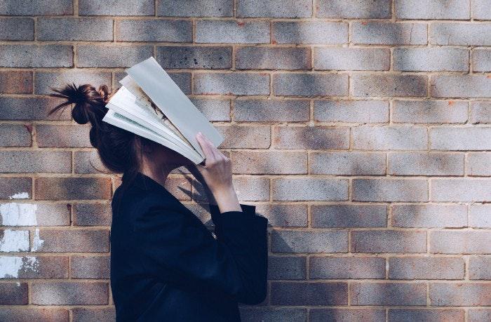 壁の前で本で彼女の顔を覆っている